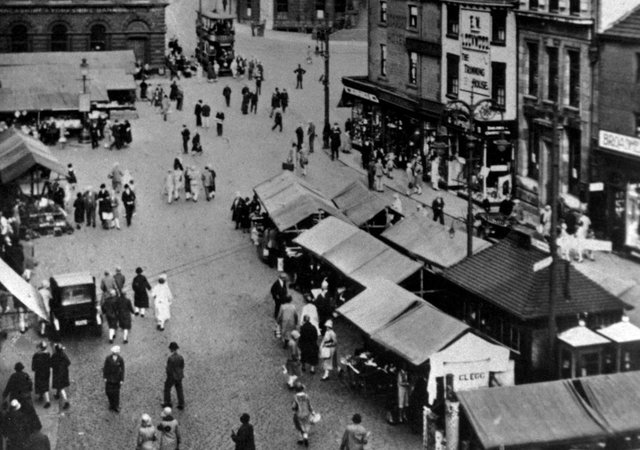 The old market site: If you have ever wondered how Market Place got its name, just take a close look at this picture and all the market stalls busily doing trade. It was moved over a hundred years ago to its present position at the other end of town.