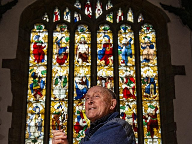 Brian Pearson with the restored medieval stained glass panels on show in the church.