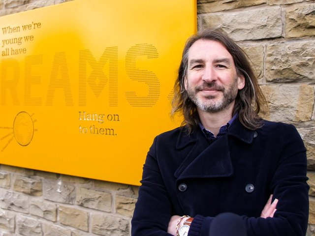 Artist Adrian Riley with the 'Dreams' art panel installed on the side of Dewsbury bus station