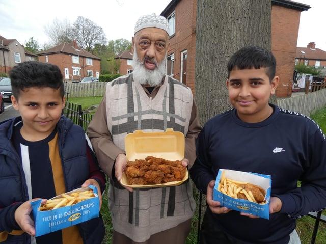 Community leader Siraj Valli giving away free chicken and chips food packs to children from Pilgrim Estate on Dewsbury Moor