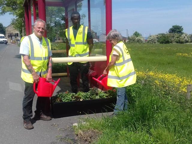 Mirfield in Bloom volunteers watering planters at the junction of Sunnybank Road and Huddersfield Road