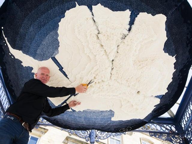Artist Andrew Warburton with his hand-woven installation in Dewsbury town centre.