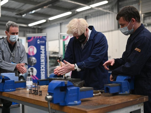Prime Minister Boris Johnson assists in an engine repair at the automotive shop during a visit to Kirklees College Springfield Sixth Form Centre in Dewsbury. Photo: Getty Images