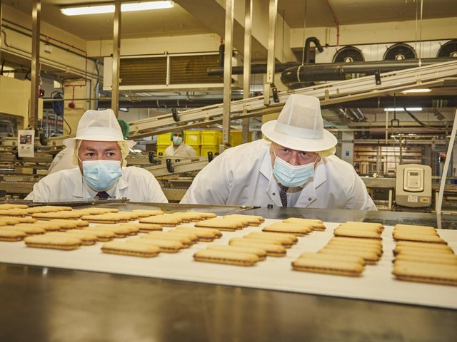 Prime Minister Boris Johnson and Ryan Stephenson, Conservative candidate in the Batley and Spen by-election, take a closer look at some of the biscuits being made at the Fox's factory in Batley. Photo by Joel Anderson