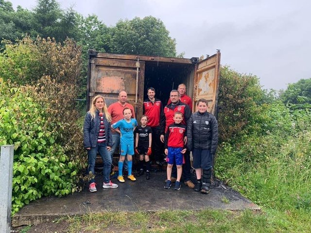 Newly elected Batley and Spen MP Kim Leadbeater with Gomersal and Cleckheaton Football Club coaches and players by the container damaged in the arson attack
