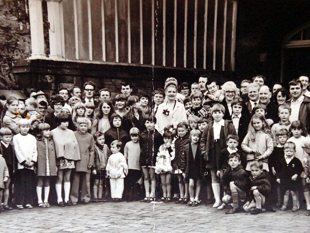 OUTING: A happy smiling group of children with their parents and patrons of the Station Hotel, Dewsbury, outside Wellington Road Station before setting off for a trip to the seaside in the 1970s. In the middle is landlady Beth Elliott with her smart beehive hairstyle. She and her husband, Ernest, were popular licensees of the Station in its heyday.
