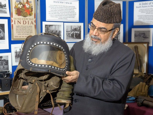 Professor Naeemi holding a Second World War infants gas mask when he visited the Ponderosa Past-Times Museum in Heckmondwike around ten years ago